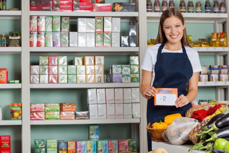 显示Pricetag的女推销员在杂货店 免版税库存图片