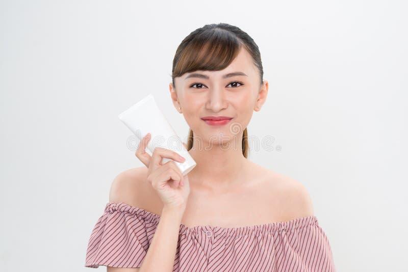 显示skincare产品的微笑的年轻女人 免版税库存图片
