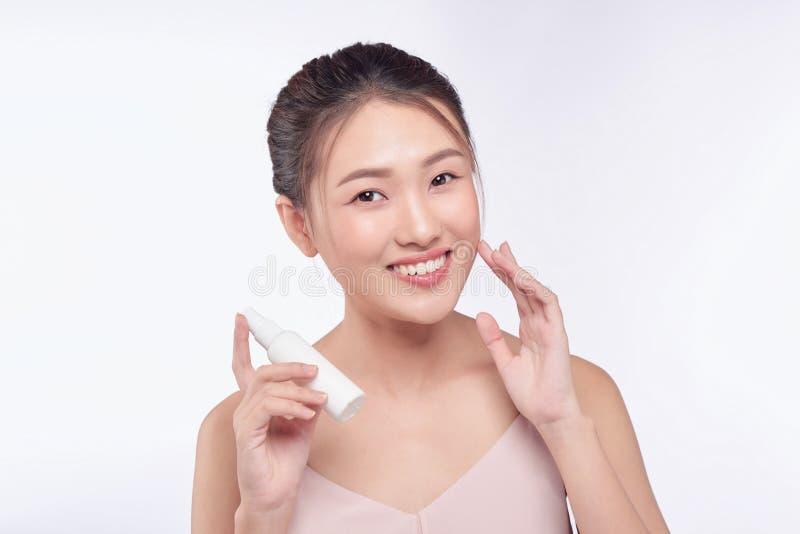 显示skincare产品的微笑的年轻女人 免版税库存照片
