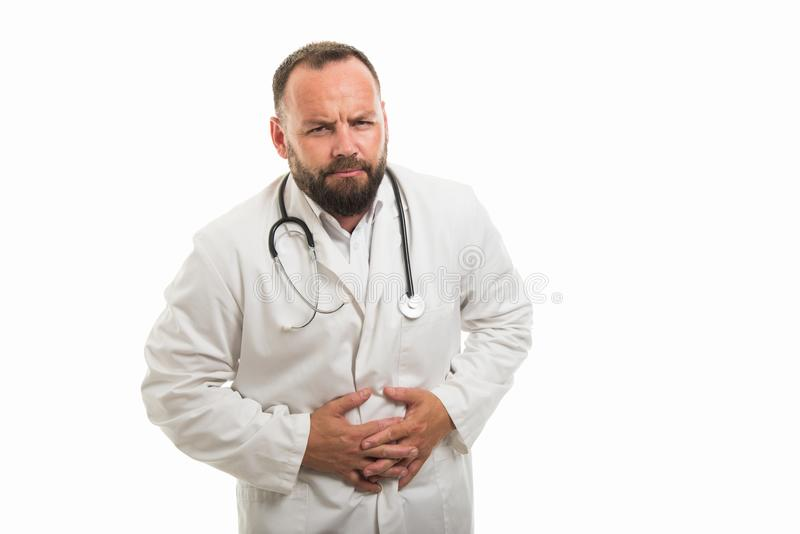 显示stomachache痛苦姿态的男性医生画象 图库摄影