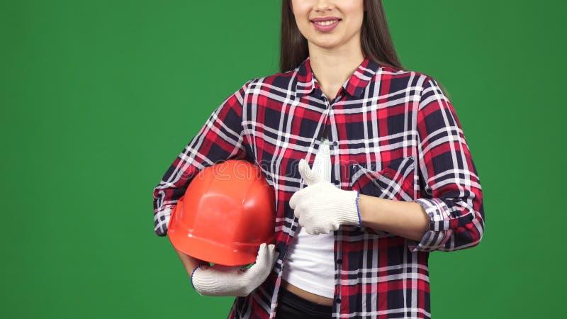 显示thimbs的一位微笑的女性工程师的播种的射击停滞安全帽 免版税库存图片