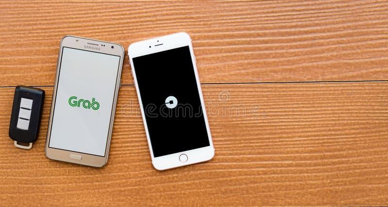 显示UBER和劫掠应用的2个智能手机 免版税库存照片