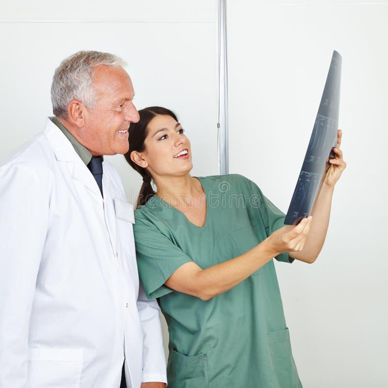 显示X-射线图象的护士对医生 免版税库存照片