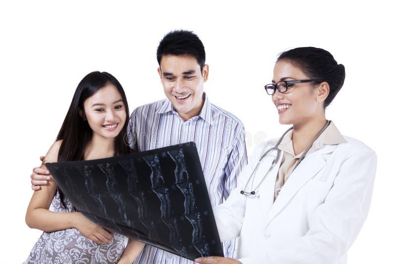 显示X-射线的一位女性医生对年轻夫妇 免版税库存照片