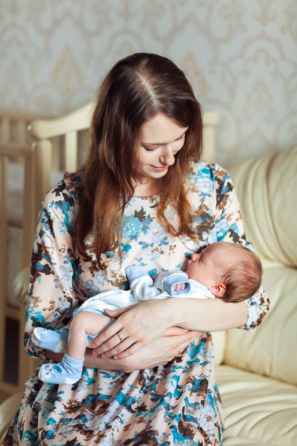 晃动她的胳膊的一个年轻母亲一个孩子 免版税库存图片