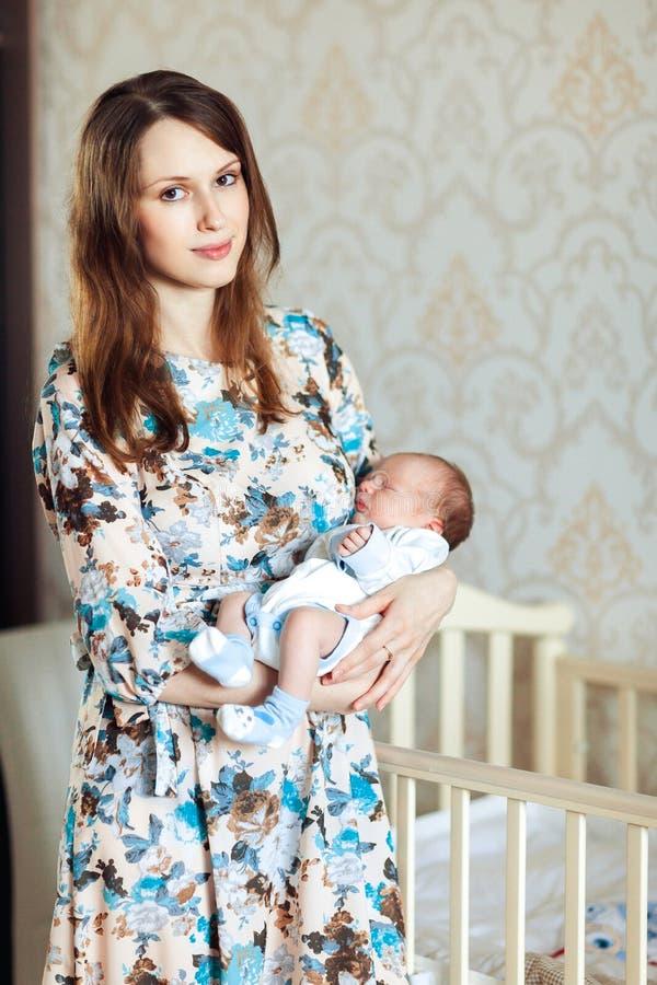 晃动她的胳膊的一个年轻母亲一个孩子 免版税库存照片