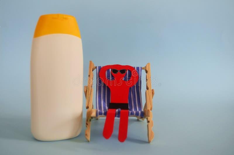 晒斑,太阳椅子的红色纸人 免版税库存图片