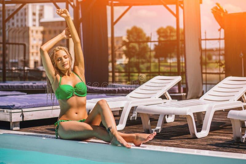 晒日光浴与她的胳膊的妇女在比基尼泳装 免版税库存图片