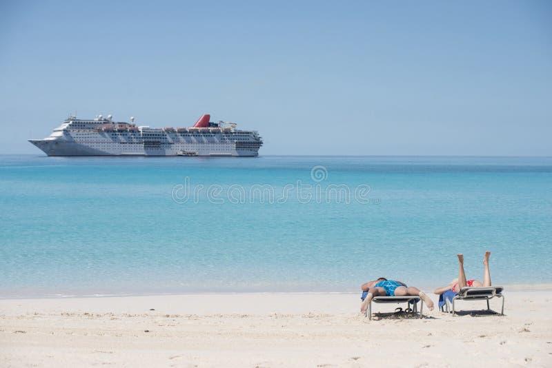 晒日光浴在与狂欢节兴高采烈的海滩的男人和妇女在背景中 免版税图库摄影