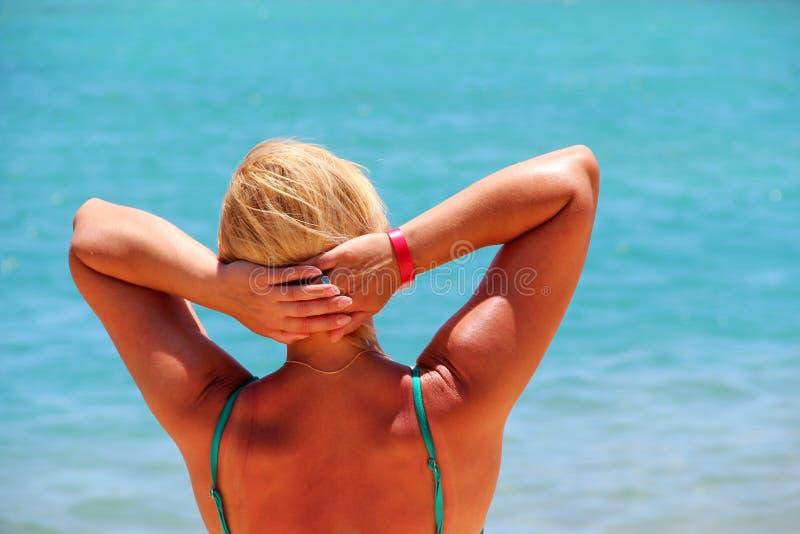 晒日光浴在太阳的女孩在假期时 享受放松的妇女海上 免版税库存图片