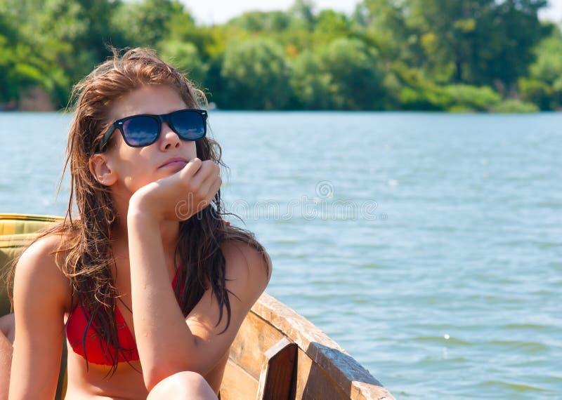 晒日光浴在小船的逗人喜爱的十几岁的女孩 免版税库存图片