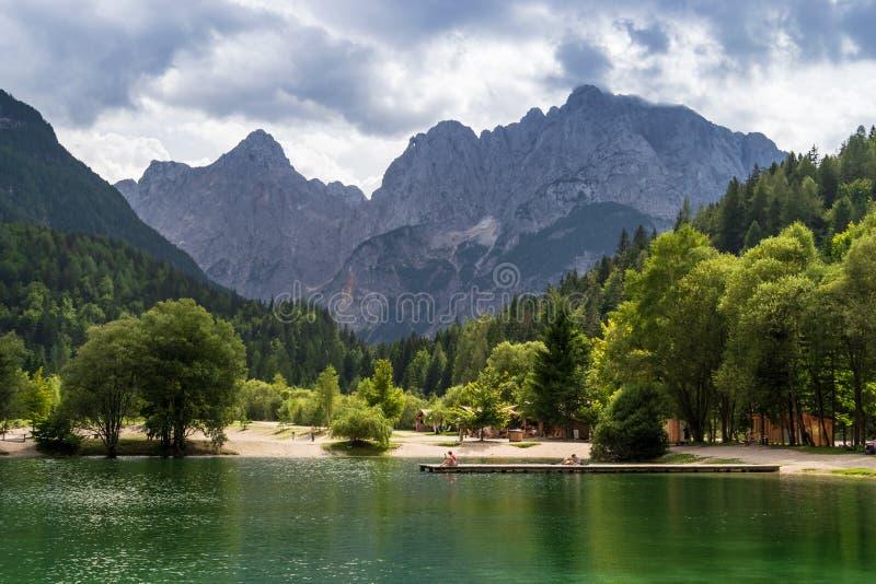 晒日光浴在木浮船的人们在有朱利安阿尔卑斯山的山峰的湖亚斯娜,在背景中 库存图片