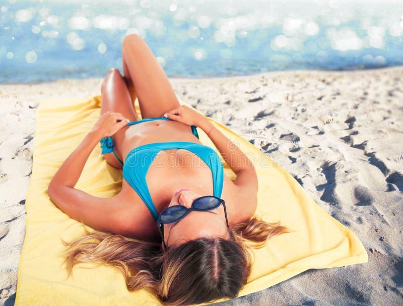 晒日光浴在毛巾的海滩的女孩 夏令时概念 免版税库存照片