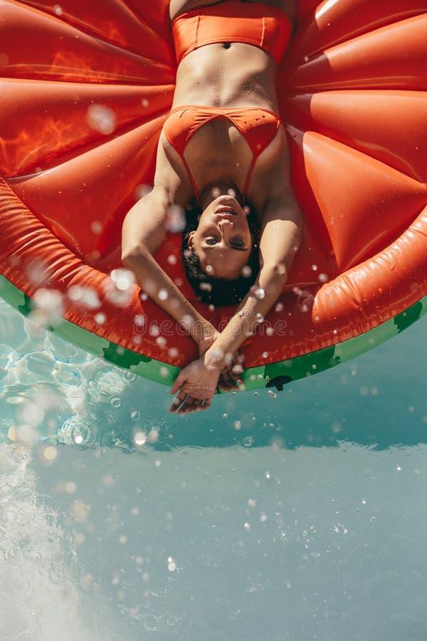 晒日光浴在水池的可膨胀的床垫的妇女 免版税库存图片