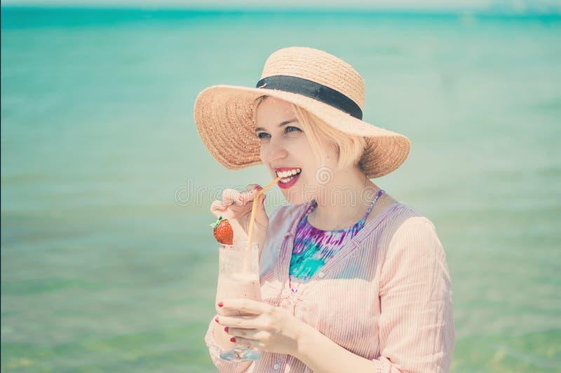 晒日光浴在海滩和饮用的汁液的年轻美女有海视图 免版税库存照片