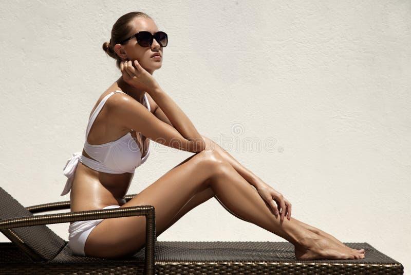 晒日光浴在海滩睡椅的被晒黑的妇女 免版税库存图片