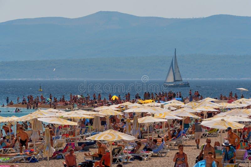 晒日光浴在海滩,克罗地亚的假日游客 库存照片