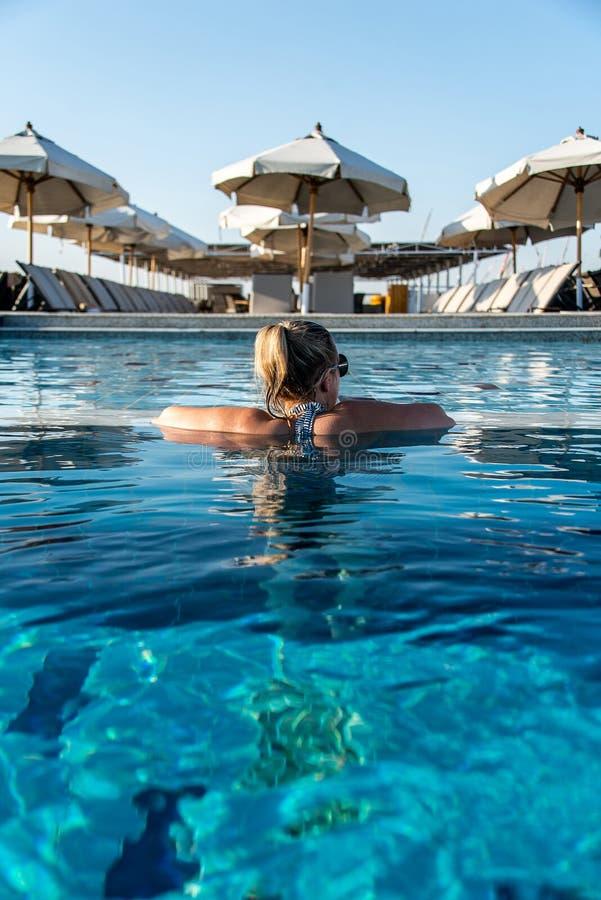 晒日光浴在游泳场的年轻美女在豪华看在遮光罩遮阳伞在埃及卢克索 免版税库存照片