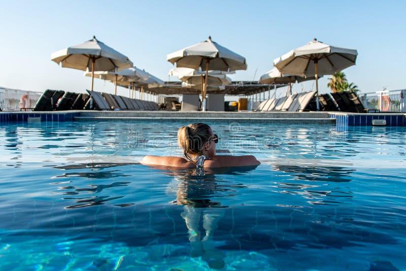晒日光浴在游泳场的年轻美女在豪华看在遮光罩遮阳伞在埃及卢克索 免版税库存图片