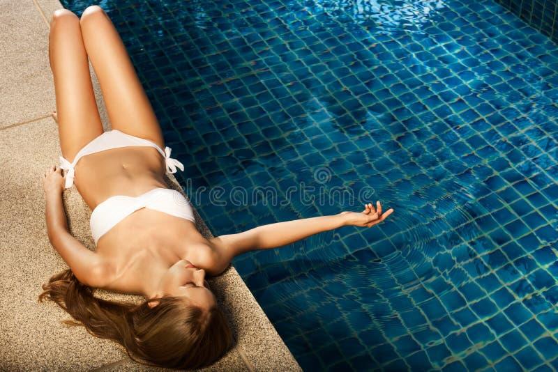 晒日光浴在游泳池附近的美丽的妇女 图库摄影