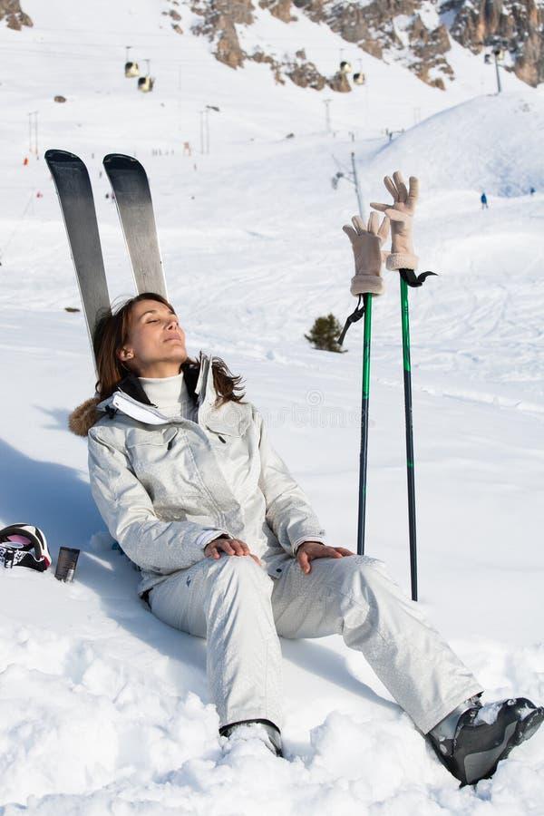 晒日光浴在滑雪倾斜的轻松的妇女 免版税库存图片