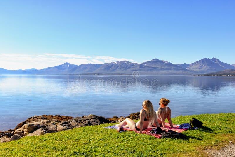 晒日光浴在特罗姆瑟南部的海滩,挪威的两个女孩 库存照片