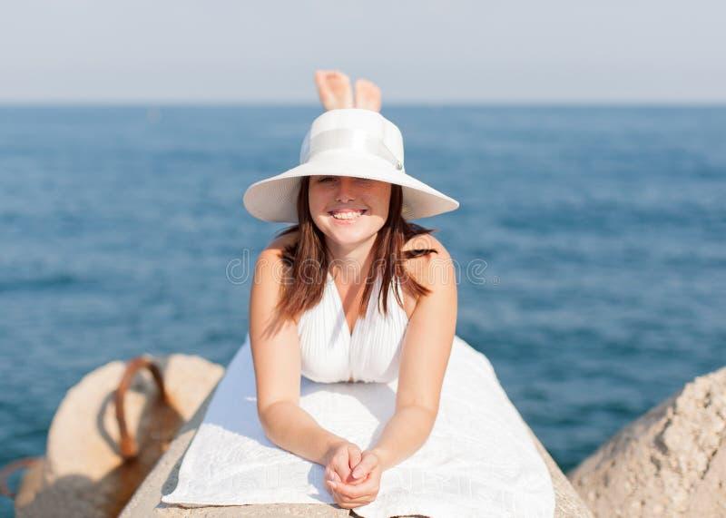 晒日光浴在防堤的女孩 免版税库存图片