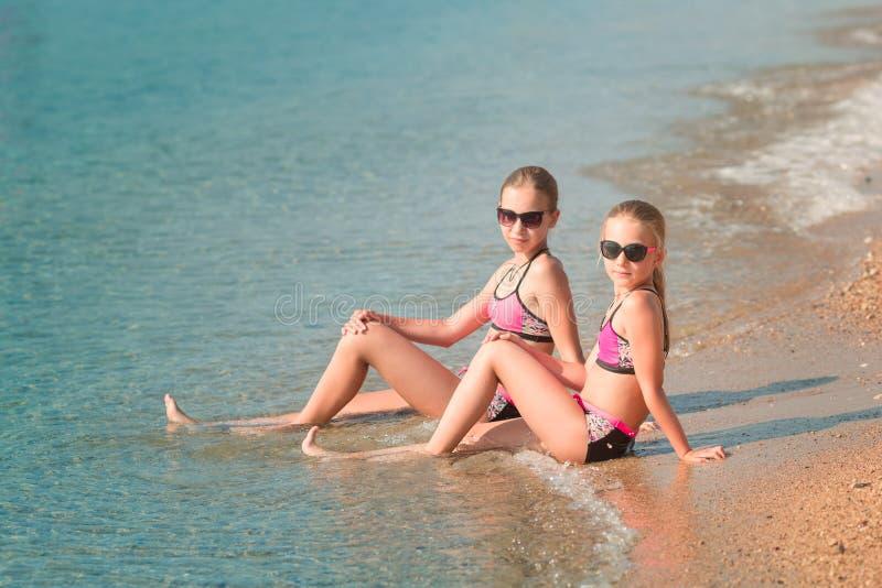 晒日光浴愉快的女孩在海边 库存照片