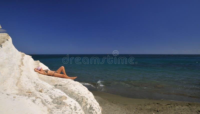 晒日光浴比基尼泳装的女孩 免版税库存照片