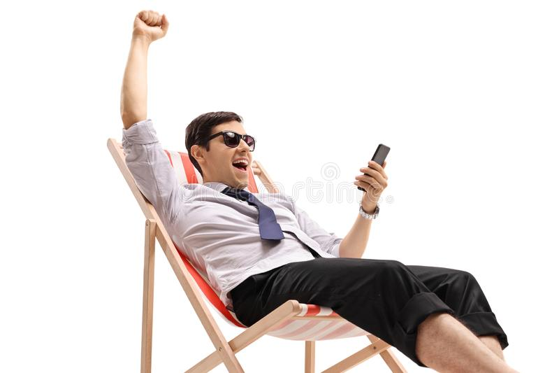 晒日光浴的商人看电话和打手势幸福 免版税库存照片
