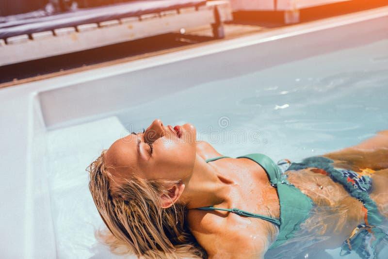 晒日光浴的游泳场的美丽的Blondie女性 免版税库存照片