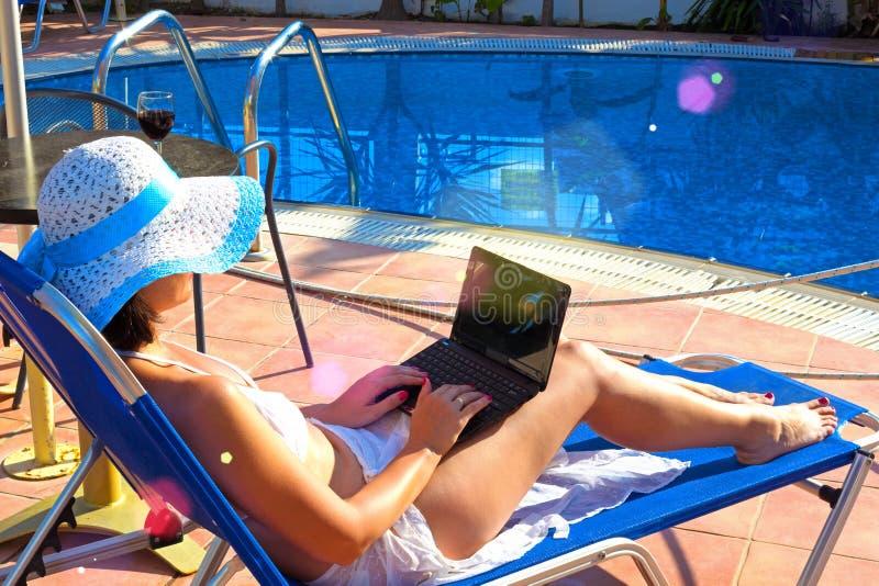 晒日光浴在与膝上型计算机的deckchair的少妇 图库摄影