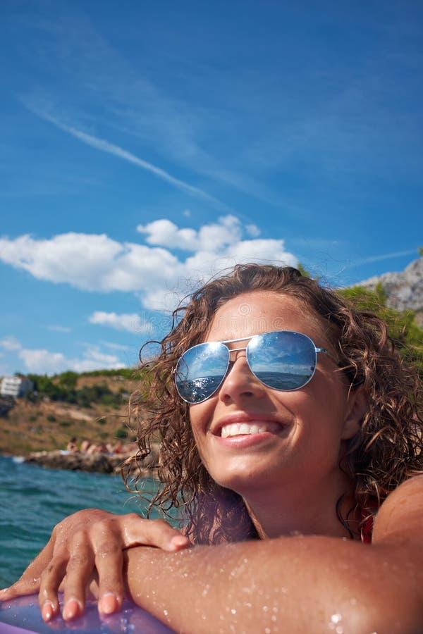 晒日光浴在亚得里亚海的水的女孩 免版税库存照片