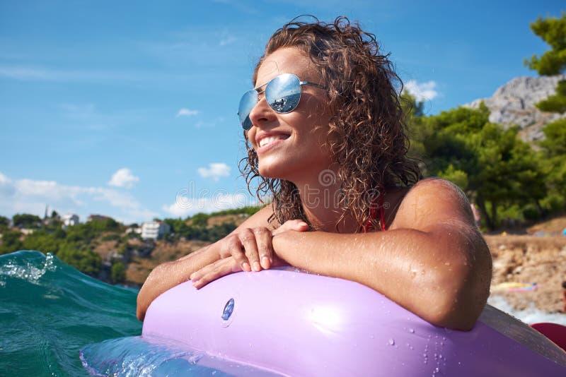 晒日光浴在亚得里亚海的水的女孩 免版税图库摄影