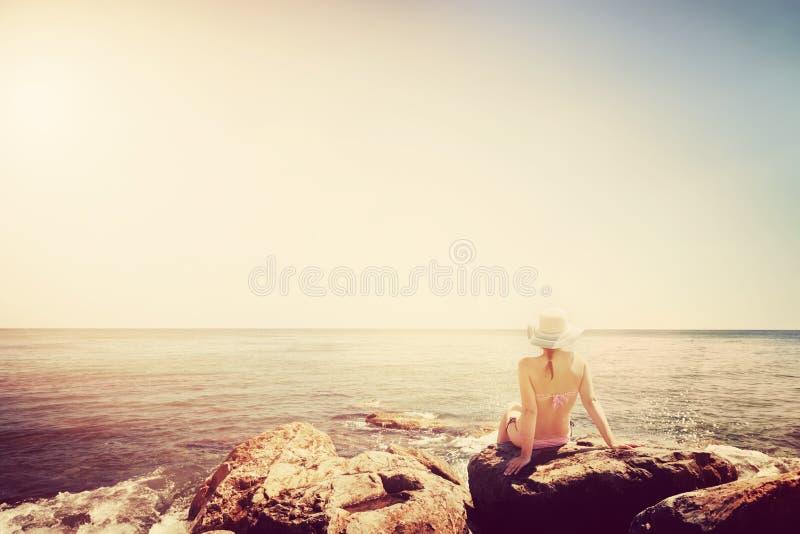 晒日光浴在多岩石的海滩的少妇 葡萄酒 免版税库存图片