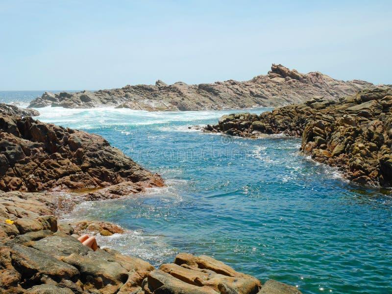 晒日光浴在岩石的人们 图库摄影