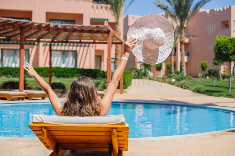 晒日光浴在懒人的愉快的妇女由水池 免版税库存图片