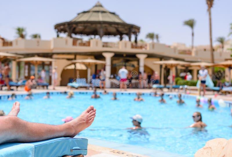 晒日光浴在手段水池的妇女 免版税库存图片