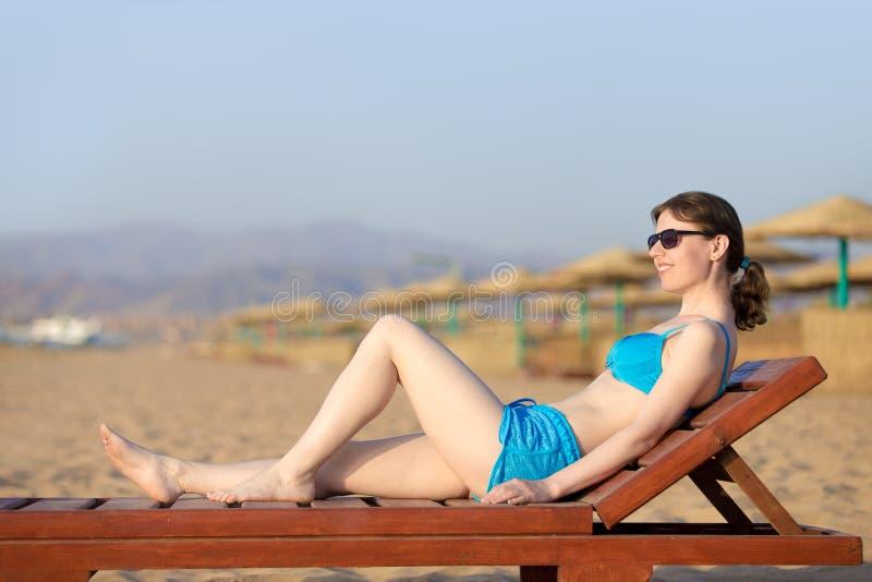 晒日光浴在木懒人的妇女 库存照片