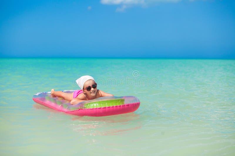 晒日光浴在桃红色空床上的小逗人喜爱的女孩  库存图片