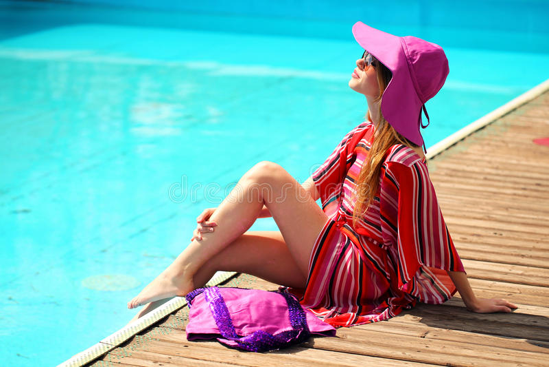 晒日光浴在比基尼泳装的妇女在热带旅行手段。说谎在太阳懒人的美丽的少妇在水池附近。 免版税库存照片