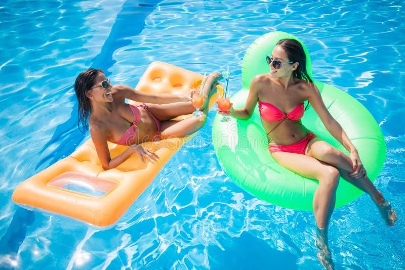 晒日光浴在气垫和饮用的鸡尾酒的女朋友 免版税图库摄影