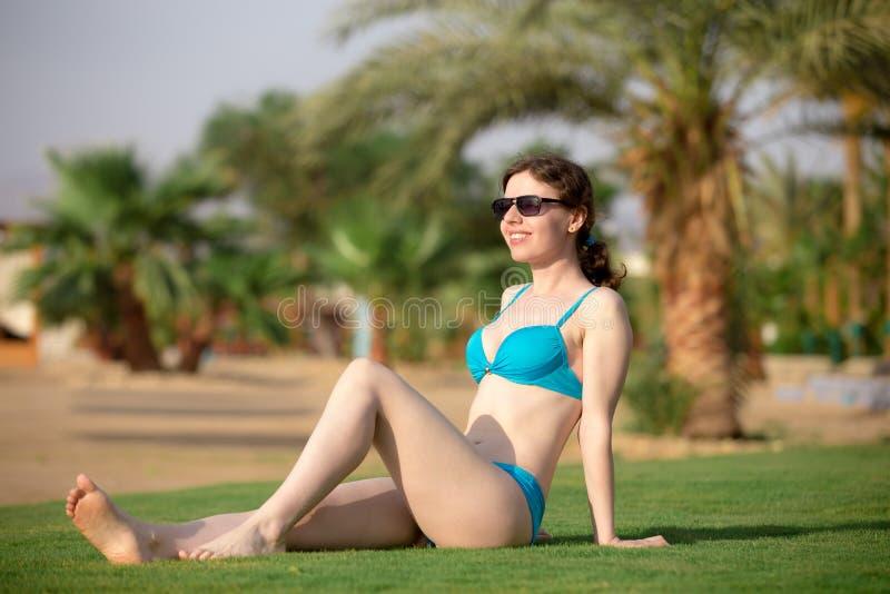 晒日光浴在海手段的女孩 库存照片