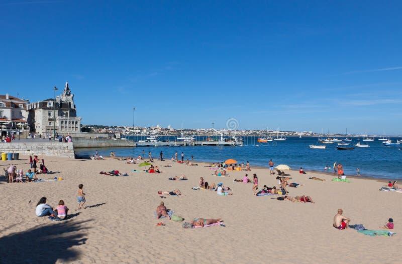 晒日光浴在海滩在卡斯卡伊斯,葡萄牙的人们 免版税图库摄影