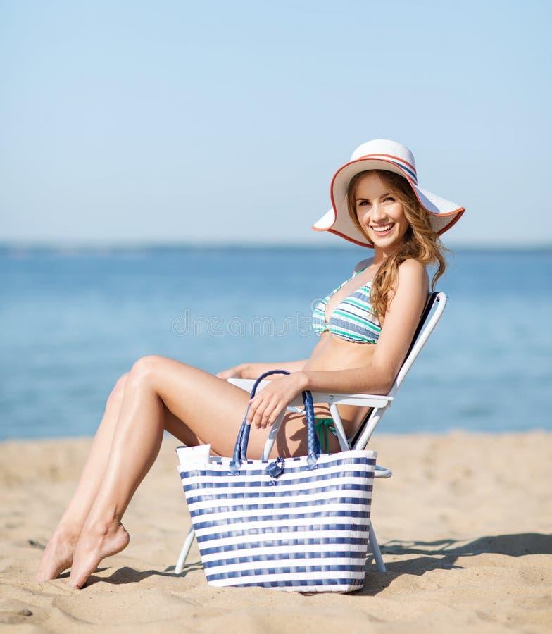 晒日光浴在海滩睡椅的女孩 免版税图库摄影