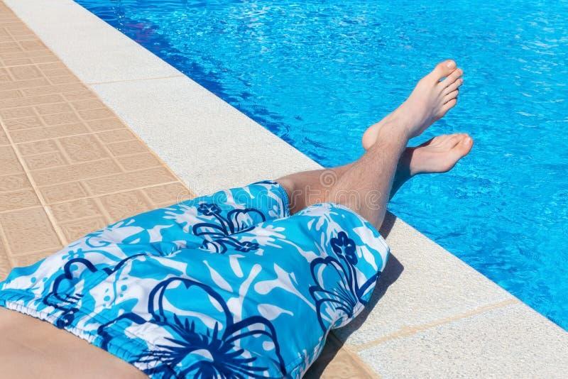 晒日光浴在游泳池的十几岁的男孩 免版税图库摄影