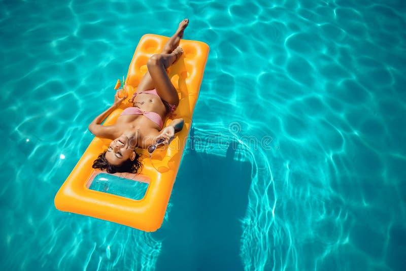 晒日光浴在游泳池的床垫的妇女 免版税库存图片