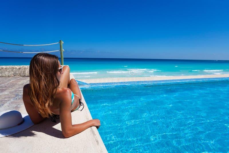晒日光浴在游泳池附近的华美的妇女 图库摄影
