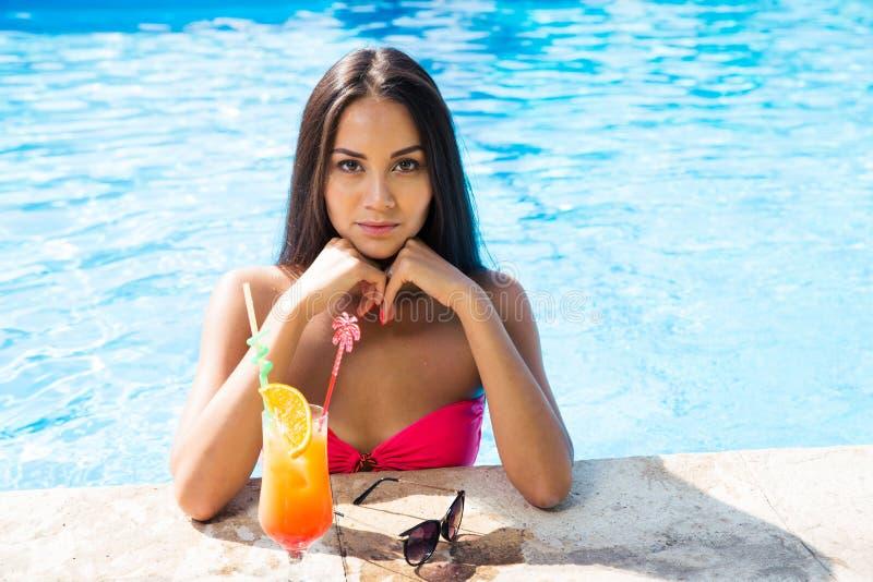 晒日光浴在游泳水池的妇女 库存图片
