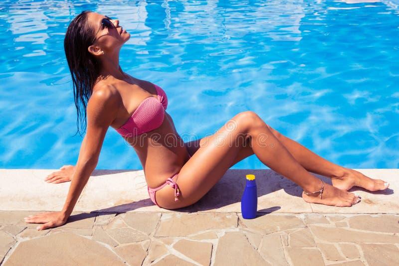 晒日光浴在游泳水池附近的妇女 免版税库存图片